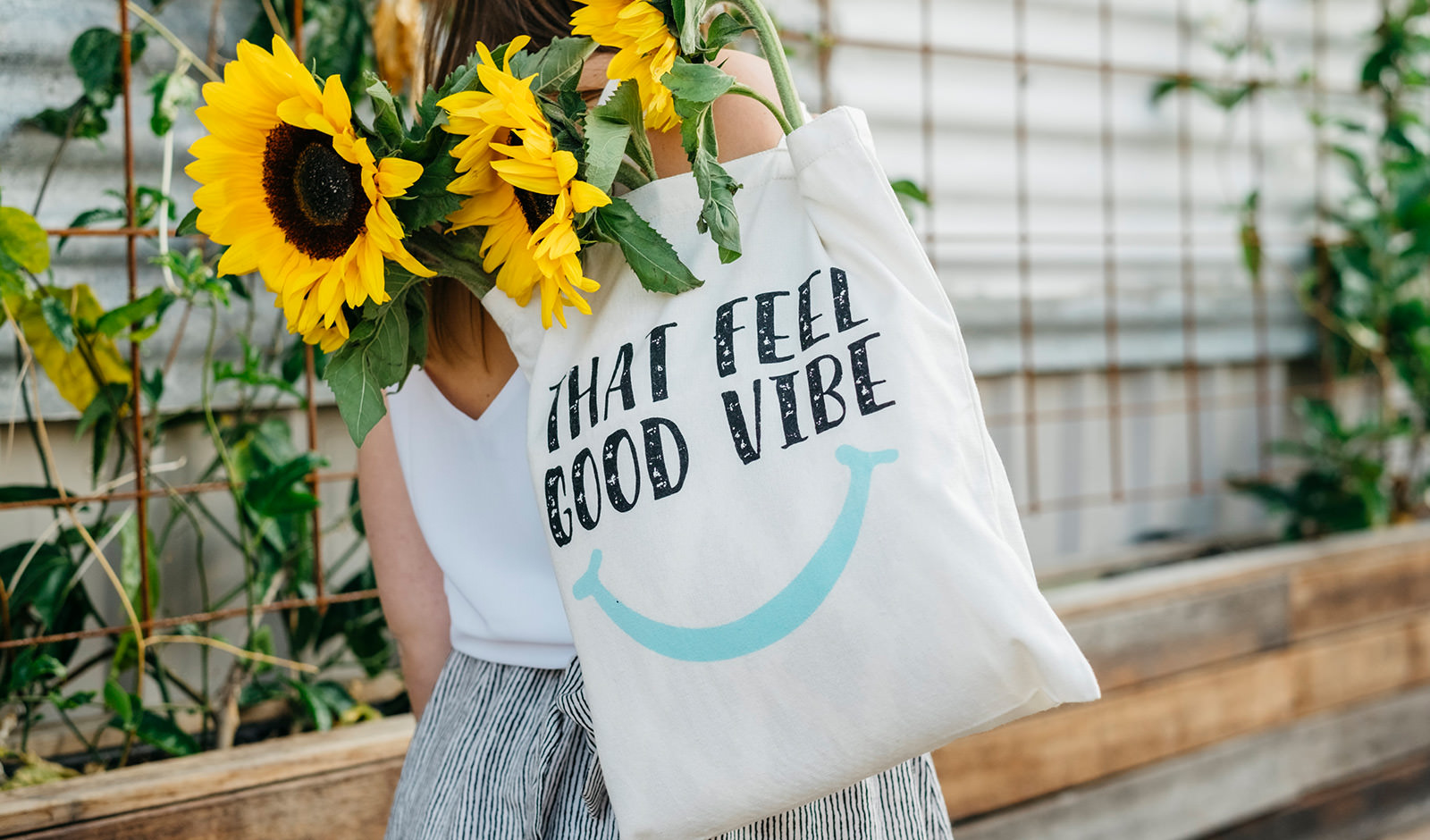 An image of a girl carrying a tote bag filled with sunflowers