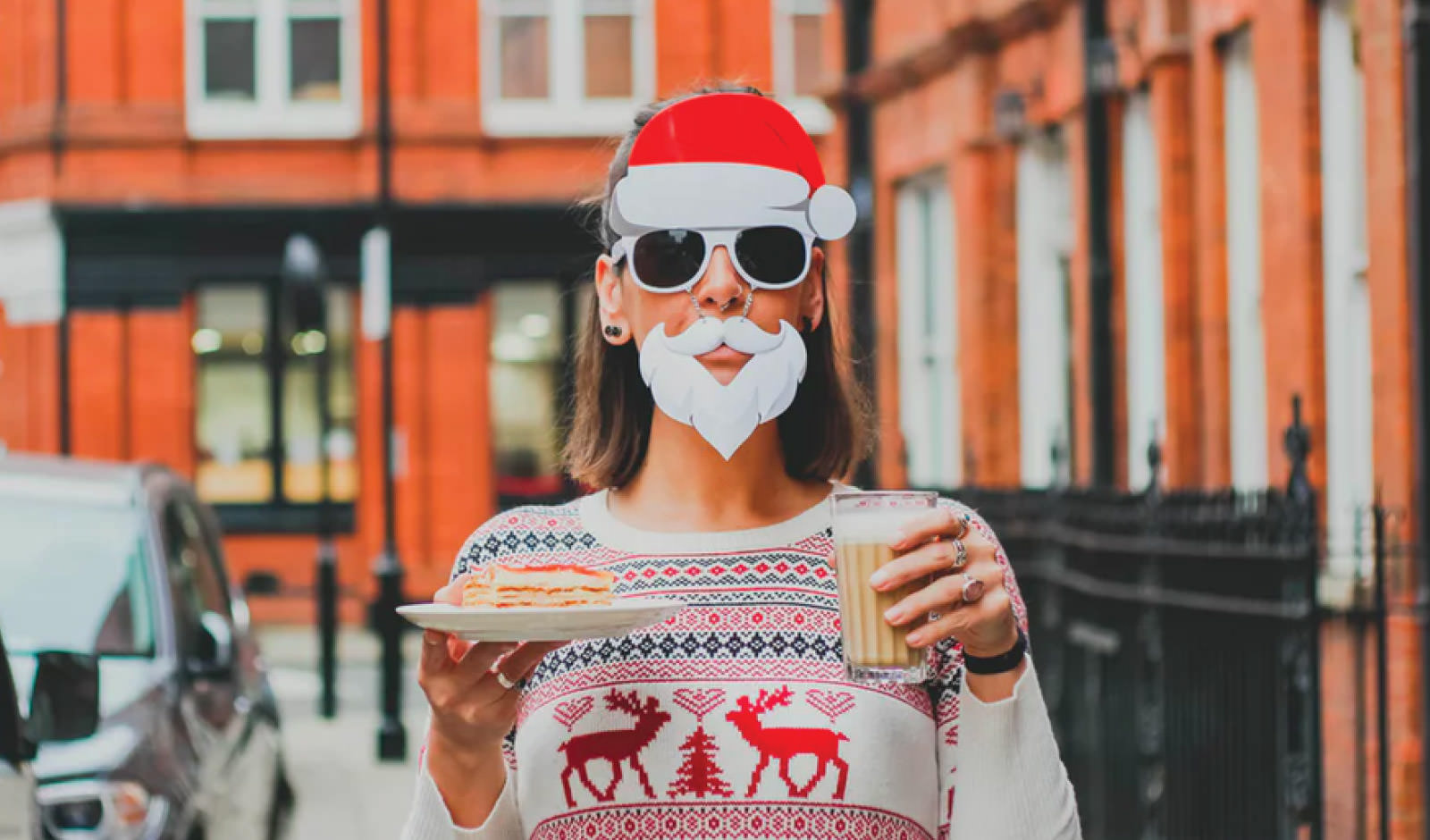 lady with a santa hat holding food and drink