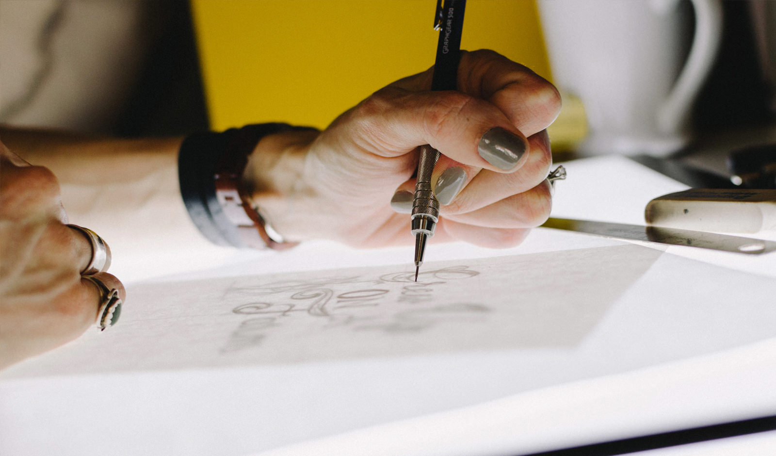 a close up image of a hand drawing on a lightbox