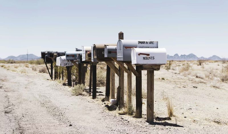 An image of post boxes on a dirt road