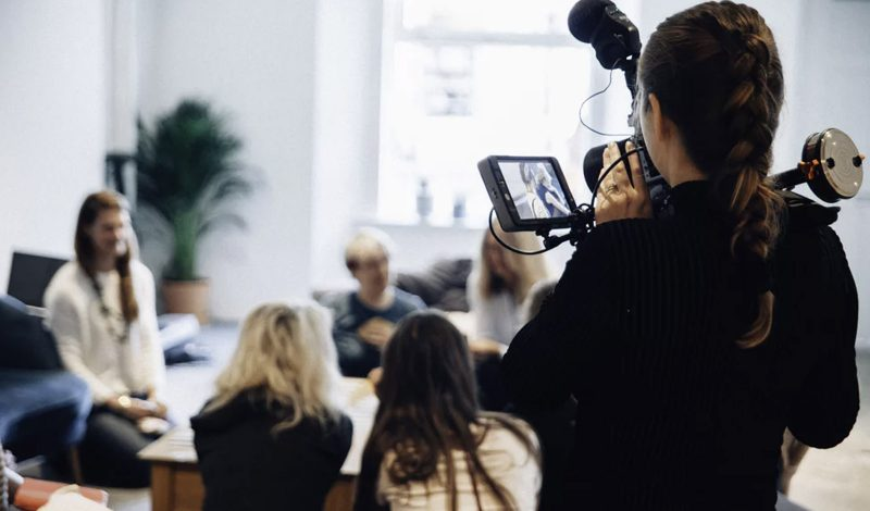 An image of a woman filming a group of professionals