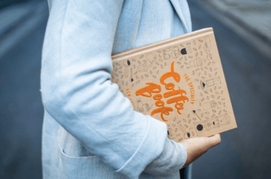 woman holding a coffee table book that Bianca designed