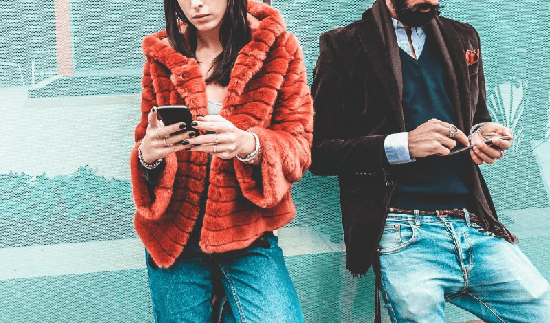 Is influencer marketing really all that? With Lemon Tree Marketing's Digital Lead Hannah Sabih. Image of a young and trendy man and woman using their mobile phones leaning against a wall.