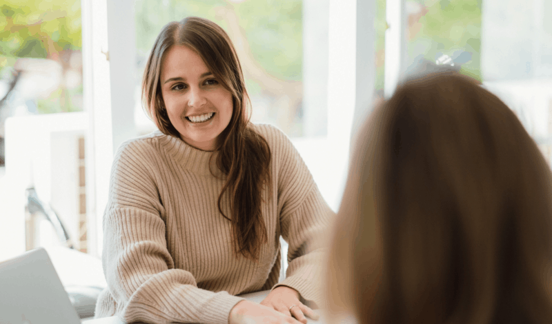 How to best communicate with your designer. Image of Lemon Tree's Creative Lead, Bianca, sitting at a table and smiling whilst talking to a client.