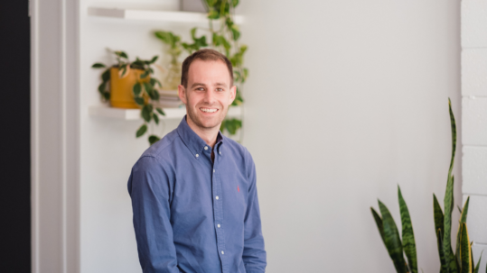 Lemon TrSocial Advertising Specialist, Josh in a blue button up shirt, sitting on a stool smiling at the camera.